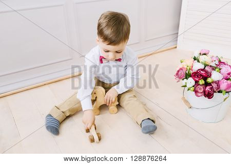 Boy playing with wooden horse sitting on the floor