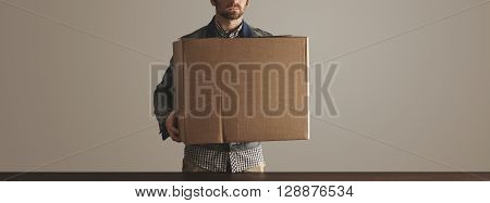 Bearded Man In Jeans Work Jacket Holds Big Carton Paper Box With Goods Above Wooden Table. Special D