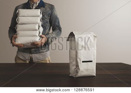 Big Sealed Hermetic Blank Labeled Package Presented In Focus In Front Of Unfocused Worker Man Loded