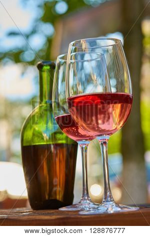 two wine glasses filled with red wine and wine bottle in background. Soft focus