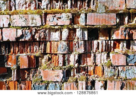Textured natural stone background - old cracked brickwork made of red brick and partly covered with green moss