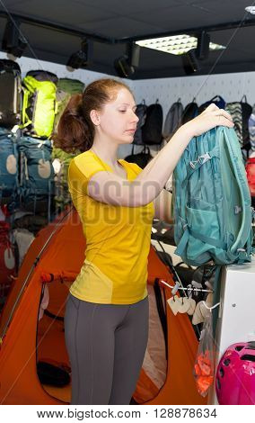 Young Caucasian girl in yellow t-shirt picks Tourist backpack in the store. Specialized products for tourism and mountaineering. The buyer on the background of a display of tents and backpacks.