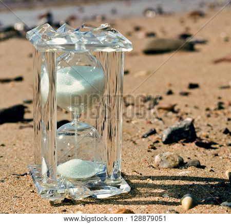 Sand-glass at sandy beach symbolizing a short time of vacation