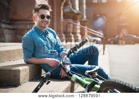 Full of joy.  Cheerful content smiling guy leaning on the footsteps   near his bicycle  and resting while expressing gladness