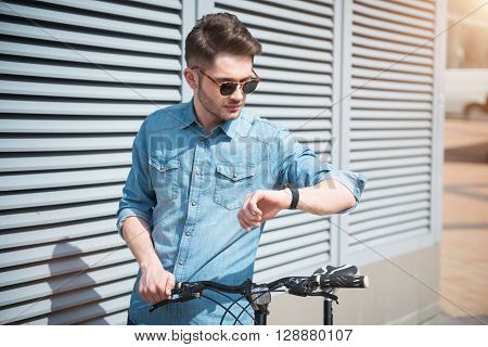 Follow your tempo. Pleasant  handsome guy looking at his wrist watch and holding bicycle while going to ride it