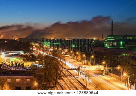 Night landscape with a road in the industrial area of the city and buildings and production halls on the background. View from the top. City Nizhny Tagil. Russia