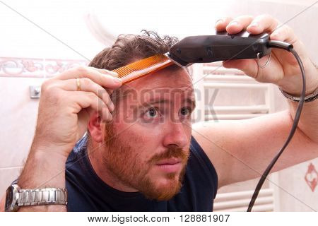 man grooming his hair with electric razor