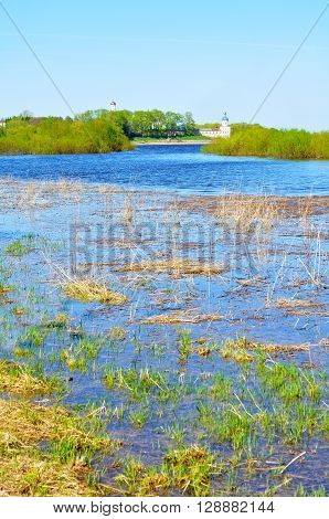 Spring rural landscape in nice sunny weather - Volkhov river and Yuriev monastery in the distance in Veliky Novgorod Russia. Architecture spring landscape.