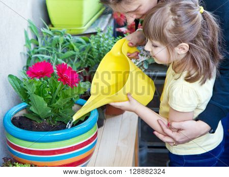 Young gil and mother watering potted flower plant smiling