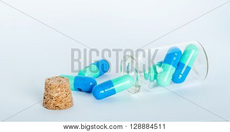 blue and green pills in small jar