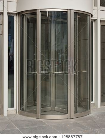 Modern revolving door as entrance to office building or hotel