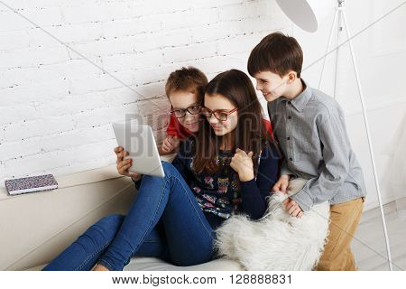 Group of kids in eye glasses look into tablet. Children computer games, social networks and media addiction concept. Girl and boys with tablet. Communication problems