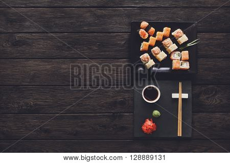 Japanese food restaurant, sushi maki gunkan roll plate or platter set. Free, copy space, chopsticks, ginger and wasabi. Sushi at rustic wood background and black stone. Top view at black. Flat lay.