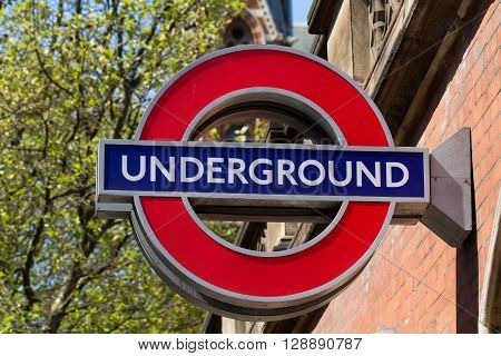 LONDON, UK - MAY 5, 2016. A London Underground sign marking the entrance to an underground train station, attached to a brick wall in the city of London.