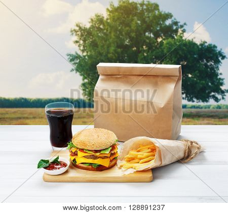 Fast food. Brown wrapping paper package with copyspace. Hamburger, potato fries, drink outdoors at picnic. Takeaway food. French fries, packaging, Cola glass, big cheese hamburger at wood.