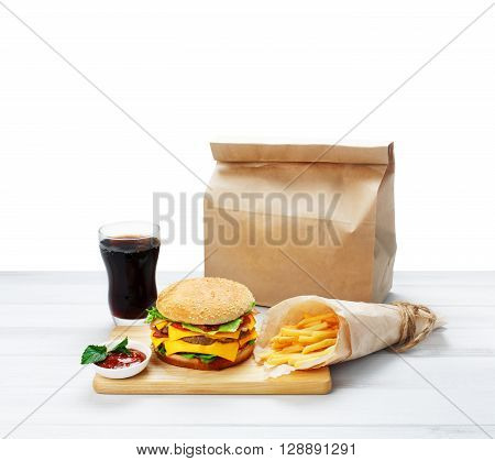 Fast food. Brown wrapping paper package with copyspace. Hamburger, potato fries isolated. Takeaway food. Wrapped French fries, packaging, Cola glass, tomato sauce, double cheese hamburger at wood.