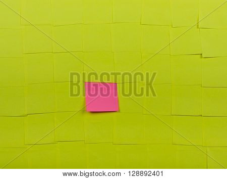 Background of yellow sticky notes. Pink sticky note is among yellow sticky notes.