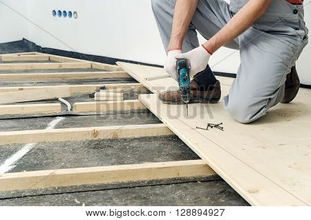 Installation of wooden floors. Worker twisting screw into the floor board.
