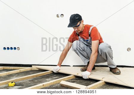Installation of the wooden floor. A worker pushes the board to the board.