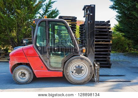 Forklift standing outdoors against the backdrop of wooden pallets and green trees