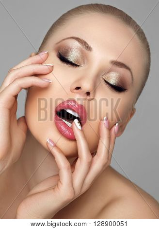 Emotional portrait of young gorgeous woman with plump lips, white straight teeth. Girl touching lips hands. Delicate French manicure. Eyes closed gold evening makeup