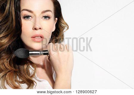 Beautiful woman holds in her hand a professional makeup brush