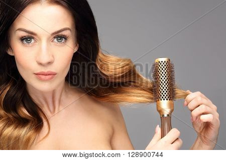 Laying, modeling hair on a round brush.