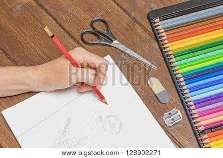 Woman`s hand is drawing a flower by a red pencil on white paper. On the wooden table are ready set of multicolored crayons in a box eraser sharpenerand scissors. ** Note: Visible grain at 100%, best at smaller sizes