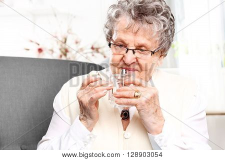 Mature well groomed woman with perfume bottle, smelling perfume.