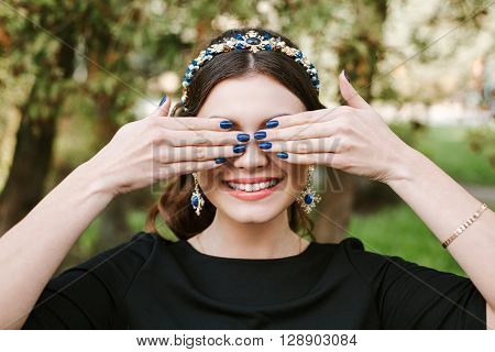 Fashion, beauty, tenderness, manicure. Young happy woman bright manicure smile wide, white smile, straight white teeth. The girl covers her face with her hands. Hair band, earrings, blue nail Polish.