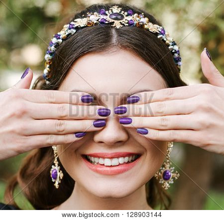 Fashion, beauty, tenderness, manicure. Young happy woman bright manicure smile wide, white smile, straight white teeth. The girl covers her face with her hands. Hair band, earrings, lilac purple Polish.