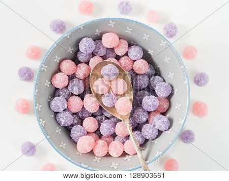 Round purple and pink bonbon candies in a bowl on white canvas background closeup