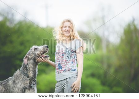 girl with the long light hair stay with a huge gray wolfdog