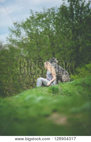 girl with the long light hair sit with a huge gray dog