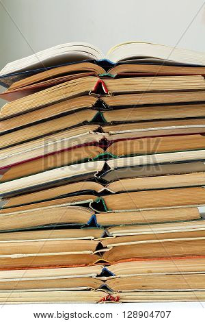 stack of opened old damaged books, vertical