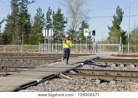 LODEYNOJE POLE, RUSSIA - MAY 2TH, 2016: Unidentified girl running railways at a pedestrian crossing on a green traffic light signal