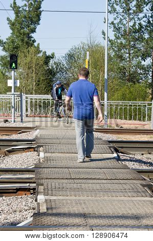 LODEYNOJE POLE, RUSSIA - MAY 2TH, 2016: An unidentified man quietly crossing the railway at a pedestrian crossing on a green traffic light signal