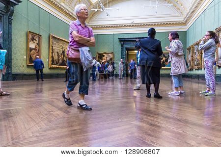 LONDON UK - JUNE 7 2015: Unidentified visitors in one of the halls of the National Gallery