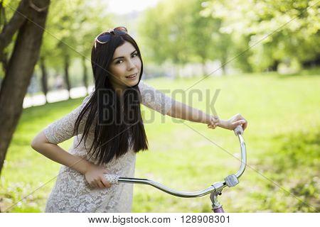 Young Woman In Sundress Enjoying Bike Trip In Park
