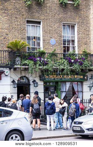 LONDON UK - JUNE 6 2015 : Unidentified people near Sherlock Holmes house and museum in 221b Baker Street. Here is where Arthur Conan Doyle located the studio of the famous detective.