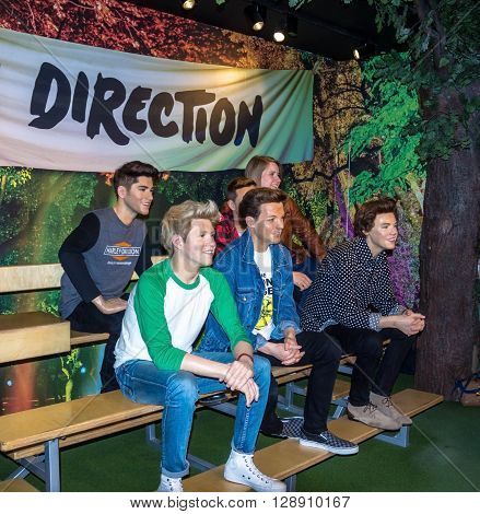 LONDON , UK - JUNE 7, 2015: Unidentified tourists make photo for memory with  One Direction band  at Madame Tussaud wax museum. London. UK
