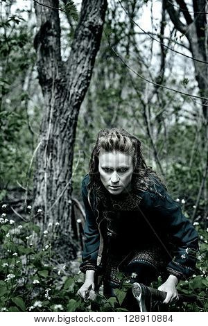 Serious and dangerous scandinavian woman posing with sword and axe in a forest
