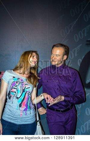 London UK - JUNE 7 2015: Unidentified girl makes photo for memory with a wax figure of Robin Williams is seen on display at Madame Tussauds