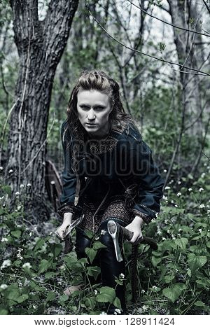 Serious brave scandinavian woman posing with axe and sword in a forest