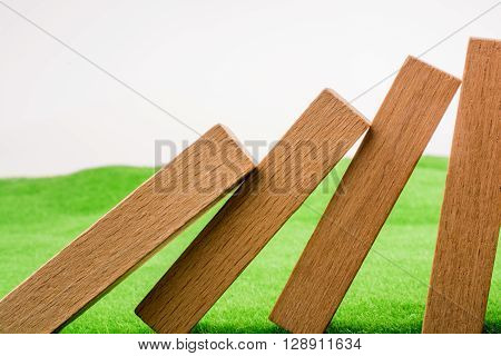 Wooden domino pieces stand on green grass