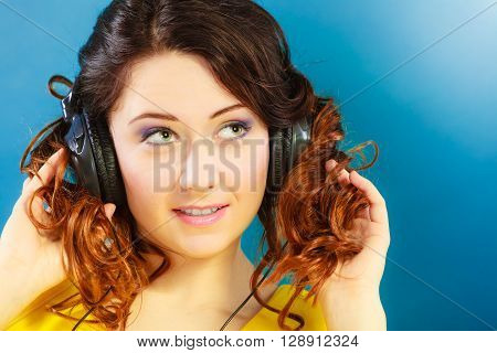Young people leisure relax concept. Closeup teen cute girl in big headphones listening music mp3 relaxing on blue background