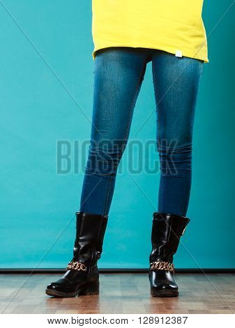 Fashion. Woman legs in denim trousers black boots casual style on blue