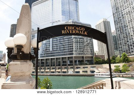 A signboard infront of Chicago Riverwalk, which is a pedestrian river waterfront in Chicago. On the background, Trump International Tower and the river is seen.