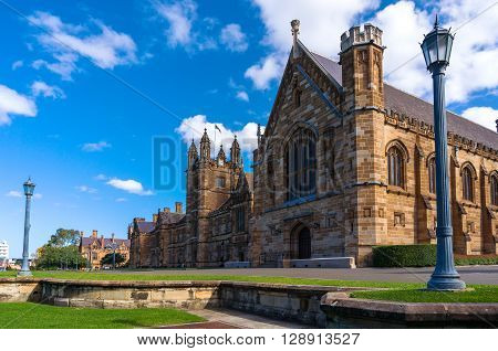 Sydney Uni building facade. University of Sydney against deep blue sky with white clouds daytime photo