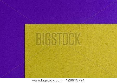 Eva foam ethylene vinyl acetate sponge plush lemon yellow surface on purple smooth background
